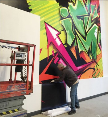 Jim Spelman installs a giant wall mural at Irontek using Solvent Print-N-Stick